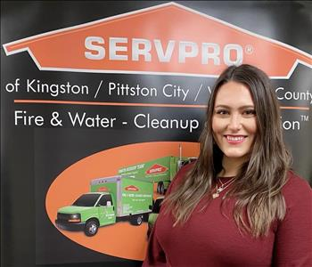 Female SERVPRO rep in front of SERVPRO sign