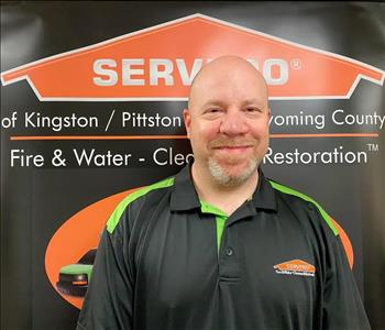 Male SERVPRO technician in front of pop up sign